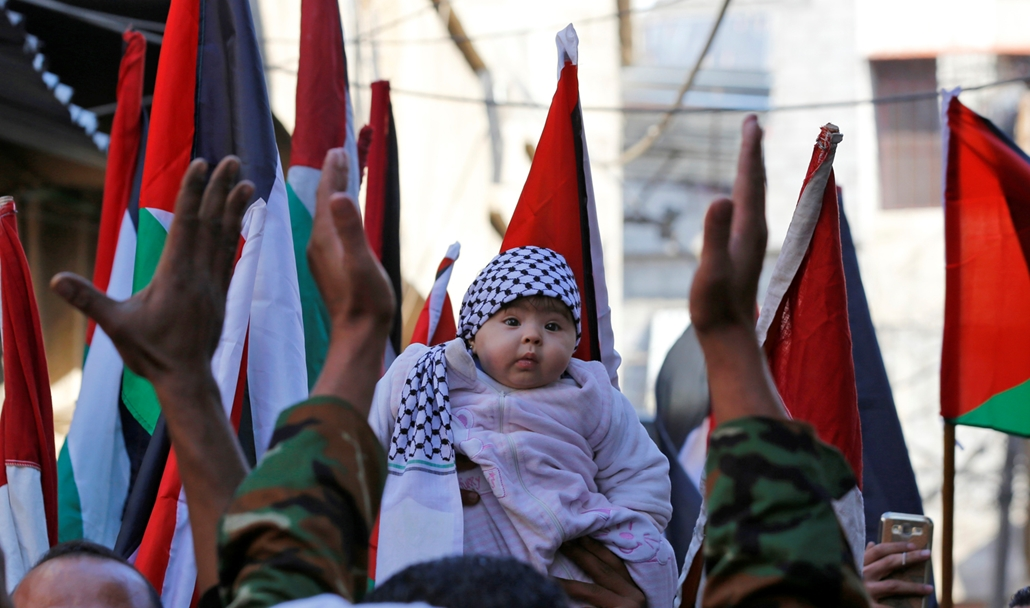 afp.17.12.08. - Egy gyereket tartanak a magasba egy jeruzsálemi tüntetésen