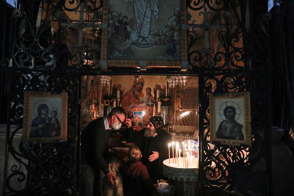 mti.21.04.02. A koronavírus-járvány miatt védőmaszkot viselő keresztény hívők imádkoznak és gyertyát gyújtanak a jeruzsálemi Szent Sír-templomban nagypénteken, 2021. április 2-án. A templomot azon a helyen építették, ahol a keresztény tanítások szerint Jé