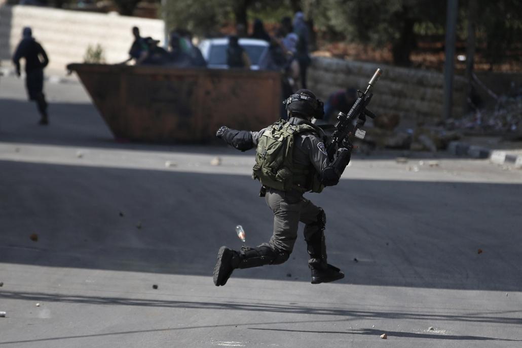 afp.izraeli-palesztin konfliktus 2015 - Beit El- 2015.10.08. Ramallah összecsapás tüntetőkkel,An Israeli security member runs as Palestinian demonstraters throw stones towards him during clashes in Beit El, near the West Bank city of Ramallah, on October