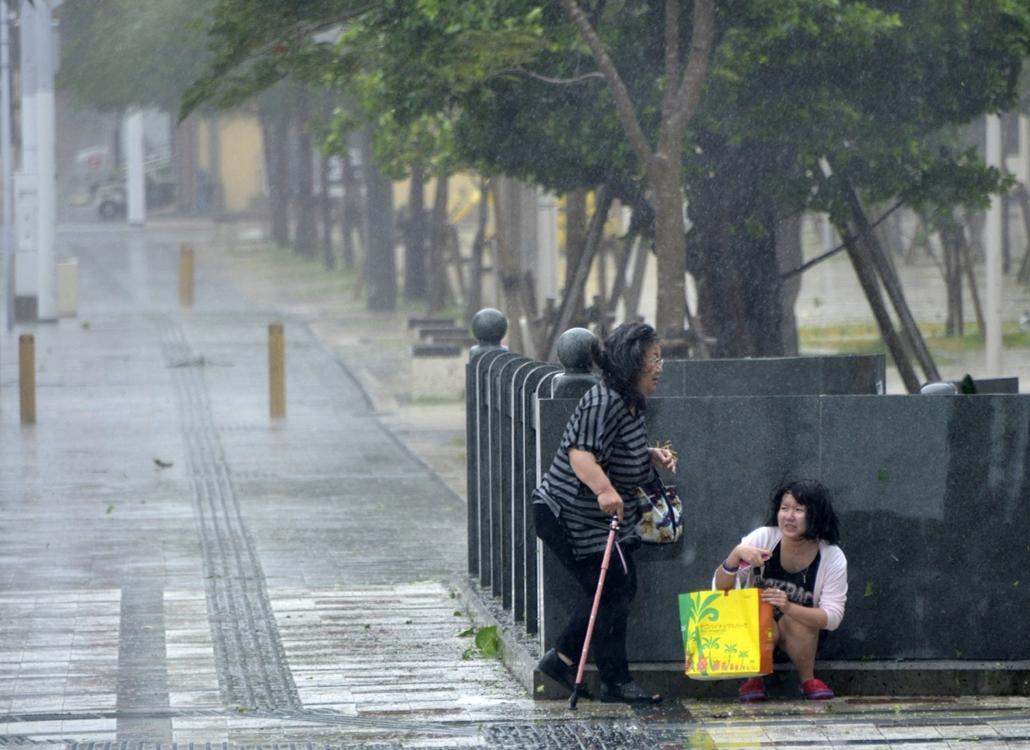 afp. szél, szeles, időjárás, nagyítás - nők bújnak el a vihar elől 2014.07.08. Naha, Japán